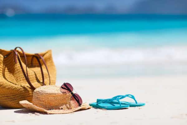 cappello borsa e infradito in spiaggia davanti al mare feriale