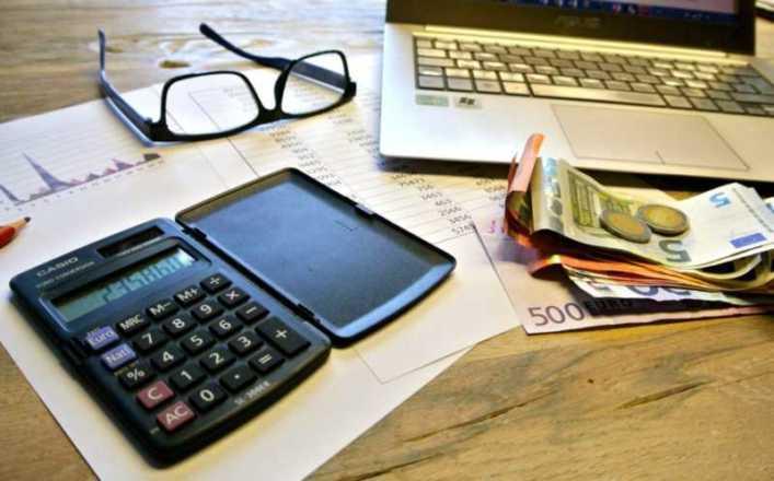 calcolatrice occhiali soldi e pc portatile