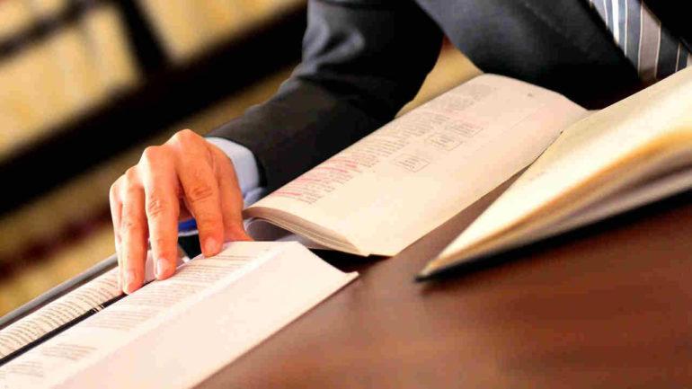 professionista alla scrivania con tre libri aperti sul pignoramento esattoriale
