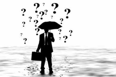 uomo con ombrello si ripara da pioggia di punti interrogativi