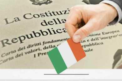 mano che inserisce la bandiera italiana nell'urna del referendum