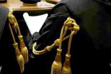due avvocati seduti con toga e cordoni oro