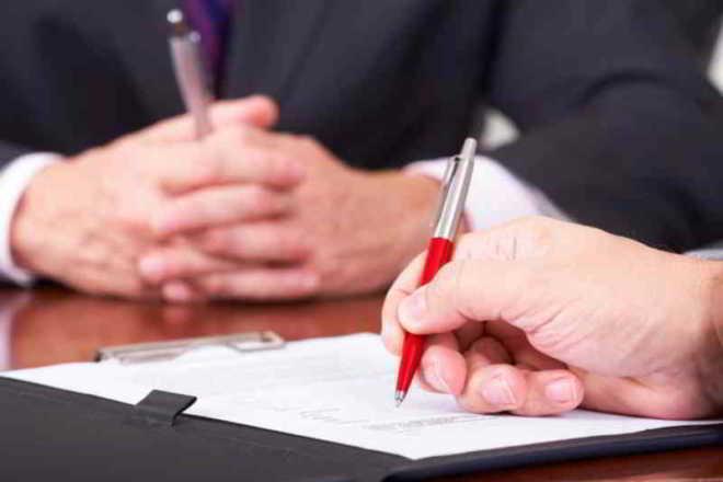 un uomo firma la polizza assicurativa