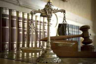bilancia della giustizia con sfondo libri di diritto