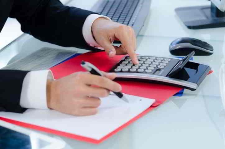 avvocato scrive preventivo con calcolatrice