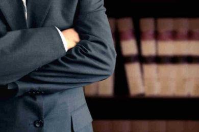 uomo in giacca e cravatta a braccia conserte